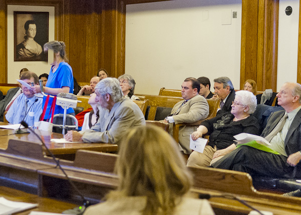 Homeless, Margaret (standing, face obscured to protect her identity) testifies at State House, Jan 2014