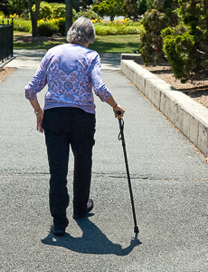Elderly woman walking with aid of a cane