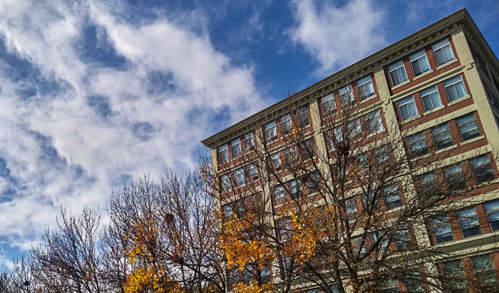 Apartment building, fall foliage, clouds