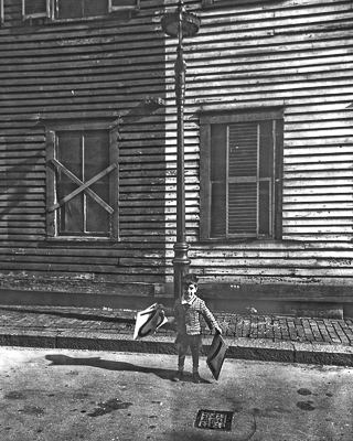 Jerry Halberstadt, 4 years old, holds number placards in front of wood frame building